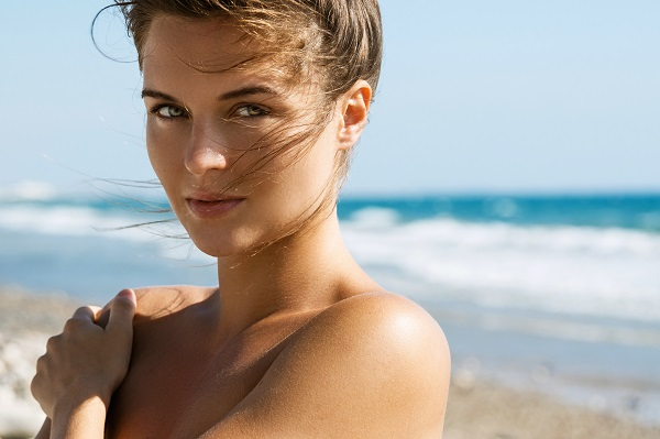 Woman at the beach topless with a close-up on the face