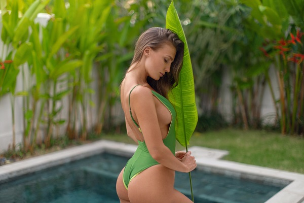 Woman in a green swimsuit holding a tropical leaf